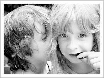 boy whispering a secret into a girl's ear