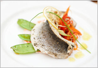 A large white plate with carefully arranged grilled seabass